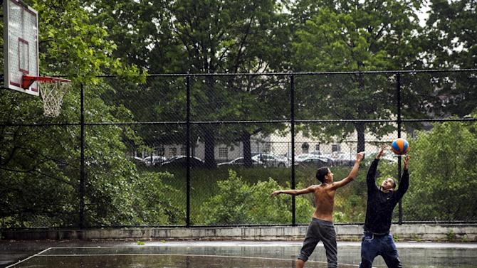 Two young men play basketball during a rain storm in New York