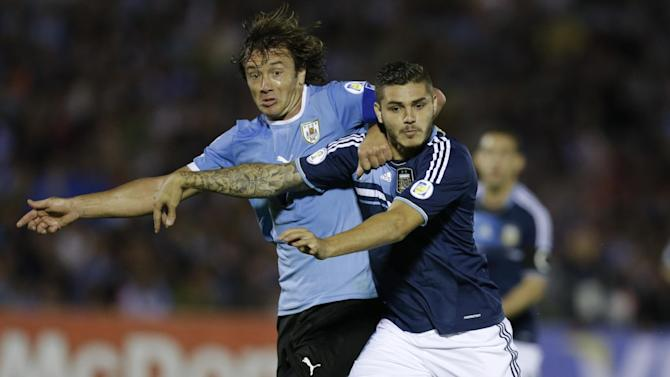 Argentina's Mauro Icardi, right, fight for the ball with Uruguay's Diego Lugano during a 2014 World Cup qualifying soccer match  in Montevideo, Uruguay, Tuesday, Oct. 15, 2013