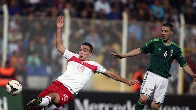 Turkey's Mevlut Erdinc, left, and Chris Baird of Northern Ireland fight for the ball during their friendly soccer match in Adana, Turkey,  Friday, Nov. 15, 2013.(AP Photo)