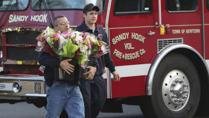 Volunteer firefighters carry flowers past their firetruck before placing them at a makeshift memorial near the Sandy Hook Elementary school Saturday, Dec. 15, 2012 in the Sandy Hook village of Newtown, Conn. The massacre of 26 children and adults at Sandy Hook Elementary school elicited horror and soul-searching around the world even as it raised more basic questions about why the gunman, 20-year-old Adam Lanza, would have been driven to such a crime and how he chose his victims. (AP Photo/Mary Altaffer)