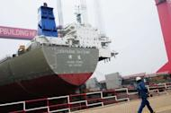 A worker walks past a freight boat under assembly at a port in Qingdao, east China's Shandong province on April 10, 2012. Further evidence of a slowdown in China's export-driven economy came with data showing output from its millions of factories and workshops rose at a much slower pace in the first three months of this year