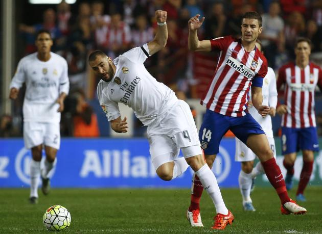 Atletico Madrid's Gabriel Fernandez is challenged by  Real Madrid's Karim Benzema during their Spanish first division derby soccer match in Madrid