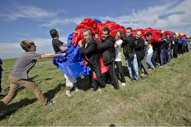 Romanians carry a huge national flag on the Clinceni Airfield, south of Bucharest,  Romania, Monday, May 27, 2013. Romania entered the Guinness Book of records after it unveiled the largest flag ever
