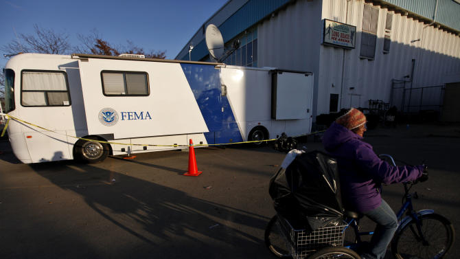 A woman pedals her loaded tricycle past a Federal Emergency Management Agency trailer after receiving relief supplies from a clothing and food distribution center, Monday, Nov. 5, 2012, in Long Beach, N.Y. (AP Photo/Jason DeCrow)