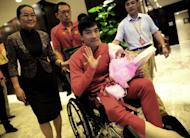 """Chinese hurdler Liu Xiang waves as he arrives back in Shanghai on August 14, 2012, after undergoing the knife in London. Liu's coach said he would make a """"full recovery"""" from his ruptured Achilles tendon, but would probably not be in action this year"""