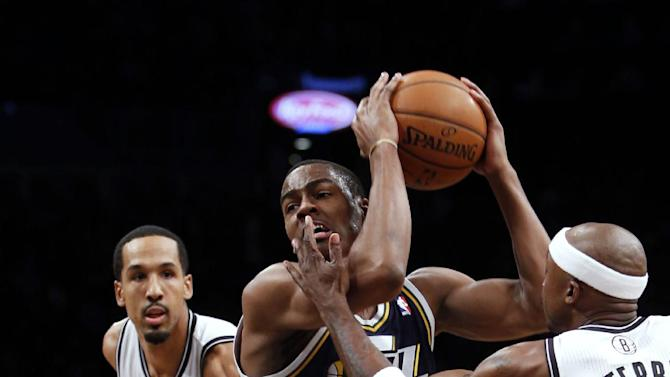 Utah Jazz's Alec Burks (10) drives between Brooklyn Nets' Shaun Livingston, left, and Jason Terry during the first half of an NBA basketball game Tuesday, Nov. 5, 2013, in New York
