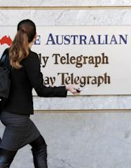 A woman walks past the entrance to the News Limited building in Sydney on June 20, 2012. The great gamble for news providers is whether larger revenues can be made from selling subscriptions to their websites or by leaving the content free and demanding more from ever-dwindling advertisers based on their traffic