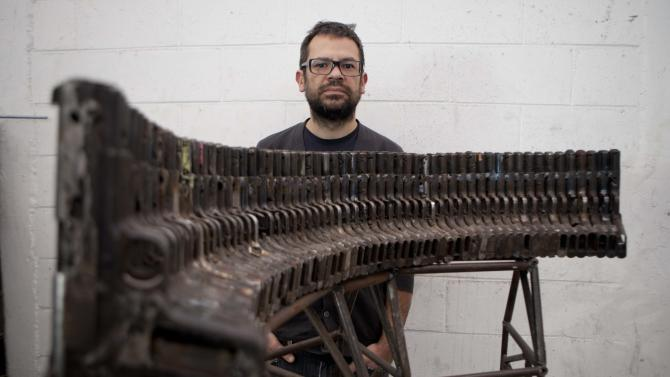 "**CORRECTS SPELLING OF BASS GUITAR** Mexican sculptor Pedro Reyes poses behind an instrument that mimics the sound of a basS guitar, made from seized guns, at his workshop in Mexico City, Tuesday, Feb. 13, 2013. The guns that have caused so many deaths in northern Mexico are transformed into musical instruments by Reyes. ""It's important to consider that many lives were taken with these weapons, as if a sort of exorcism was taking place,"" says Reyes in a description of his project titled, ""Disarm."" The Mexican artist said he was able to choose his instruments from about 6,700 guns that were turned in or seized by the army and police in Ciudad Juarez, a city of about 1.3 million people that averaged about 10 killings a day at the height of the violence. (AP Photo/Eduardo Verdugo)"