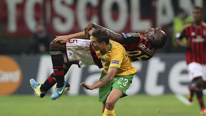 AC Milan's Mario Balotelli  is fouled by Celtic's Mikael Lustig during the Champions League group H soccer match between AC Milan and Celtic, at the San Siro stadium in Milan, Italy, Wednesday, Sept. 18, 2013