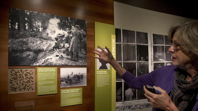 "In this Thursday, April 25, 2013 photo, museum curator Susan Bachrach discusses a group of photographs showing a local Ukrainian auxiliary policeman killing a Jewish woman and child in 1941, during a preview of the new exhibit ""Some Were Neighbors: Collaboration & Complicity in the Holocaust"" at the United States Holocaust Memorial Museum, in Washington. The exhibition opens April 30, 2013, and is about collaboration and complicity in the Nazi genocide, including interviews with some perpetrators. (AP Photo/Carolyn Kaster)"