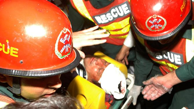 Rescue workers rush Imran Khan, Pakistan's cricket star-turned-politician, to a hospital in Lahore, Pakistan on Tuesday, May 7, 2013. One of Pakistan's most prominent politicians, former cricket star Imran Khan, fell from a stage at a political rally Tuesday, leaving him with two hairline skull fractures and uncertainty hanging over his ability to campaign ahead of Saturday's general election.(AP Photo/M.S. Shah)
