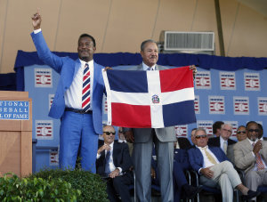 Hall of Fame inductee Pedro Martinez, left, holds the flag of the Dominican Republic with countryman and fellow Hall of Famer Juan Marichal on Sunday. (AP)
