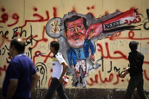 Egyptian protesters walk past graffiti against Mohamed Morsi on the wall of the presidential palace in Cairo