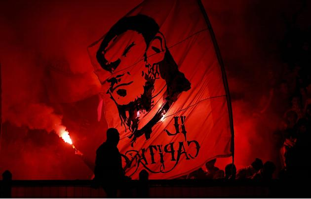 Fans of AS Roma wave a flag with the likeness of Francesco Totti on it during an intra-team exhibition soccer match in Jakarta, Indonesia
