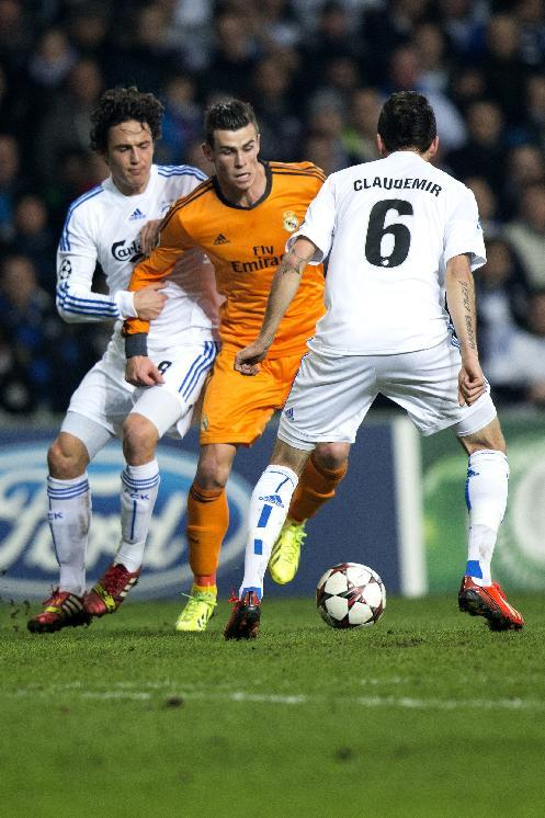 Real Madrid's Gareth Bale, centre vies for the ball with FC Copenhagen's Thomas Delaney, background and Claudemir  during the Champions League, Group B, soccer match between FC Copenhagen and Real Madrid, at Parken in Copenhagen, Denmark, Tuesday Dec. 10, 2013