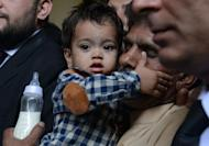 Nine month Pakistan toddler Mohammad Musa is held by his grandfather Muhammad Yasin for a court hearing in Lahore on April 12, 2014