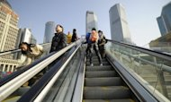 Tourists ride an escalator in Pudong, the financial district of Shanghai. The IMF has said Asia should be ready to tighten monetary policies if overheating pressures emerge, while remaining alert to any future shocks from a still volatile global climate