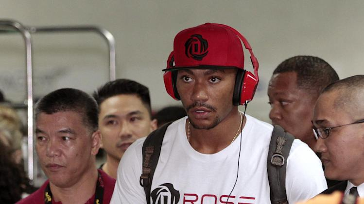 NBA star Derrick Rose of Chicago Bulls, center, walks at the arrival area of Manila's International Airport, Philippines on Saturday, Sept. 14, 2013. Rose is in the country as part of the Asia leg of his promotional tour