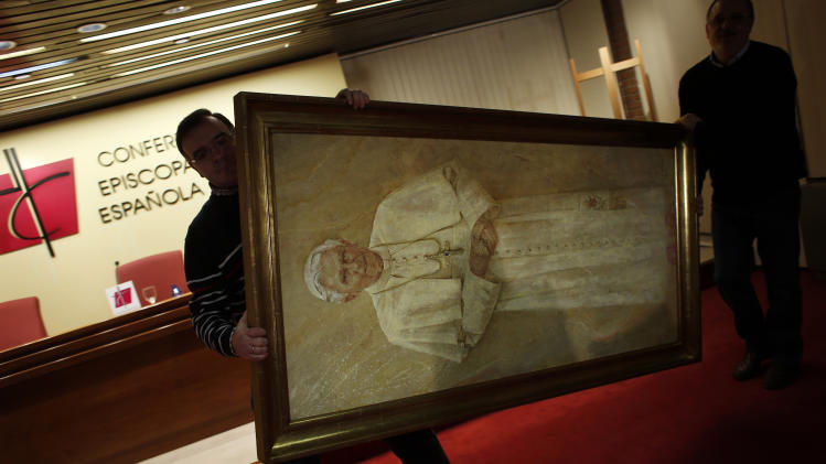 Workers remove a painting of Pope Benedict XVI from the press conference room after the head of Spain's Catholic Church and President of the Bishops' Conference Cardinal Antonio Maria Rouco Varela addressed a news conference in Madrid