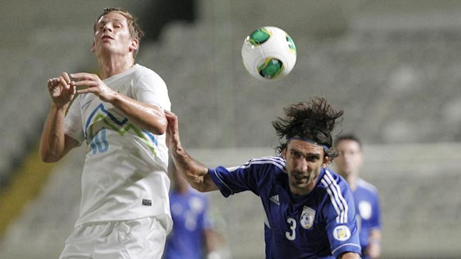 Cyprus' Elias Charalambous, right, challengers for the ball with Slovenia's Valter Birsa during their World Cup group E qualifying soccer match at GSP stadium in Nicosia, Cyprus, Tuesday, Sept. 10, 2013