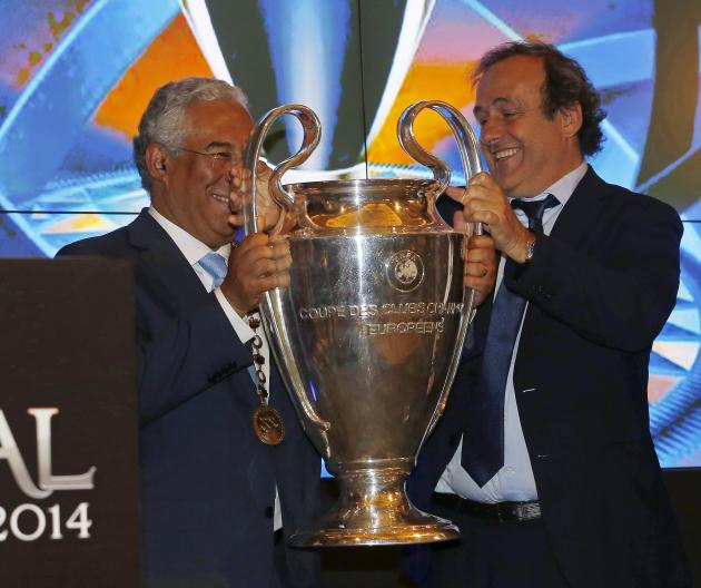 UEFA President Platini presents the UEFA Champions League trophy to Lisbon Mayor Costa during a trophy handover ceremony in Lisbon