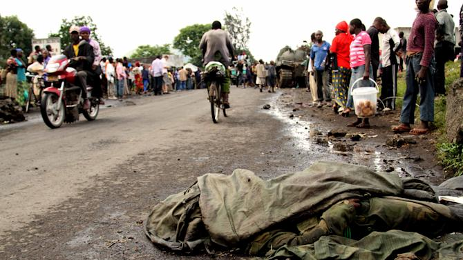 The corpse of a Congolese government soldier lies on a road linking the provisional capital Goma with Sake, in eastern Congo, Wednesday, Nov. 21, 2012. The soldier was killed after government forces retreated from an assault on Goma by the M23 rebels, who successfully captured the strategic city on Tuesday. Thousands of Congolese soldiers and policemen defected to the M23 rebels Wednesday, as rebel leaders vowed to take control of all Congo, including the capital Kinshasa.(AP Photo/Marc Hofer)