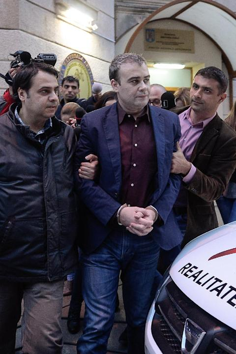 In this picture taken on Wednesday, March 25, 2015, former Romanian finance minister Darius Valcov exits handcuffed from the prosecutors office in Bucharest, Romania.   Romanian prosecutors investigat