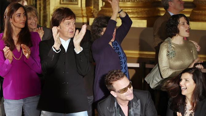 From left, Nancy Shevell, Sir Paul McCartney, Bono, and Ali Hewson applaud fashion designer Stella McCartney's Fall/Winter 2013-2014 ready to wear collection, in Paris, Monday, March, 4, 2013. (AP Photo/Thibault Camus)
