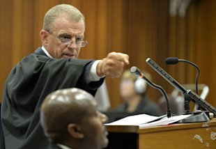Gerrie Nel gestures as he demonstrates the firing of a gun during trial. (AP)
