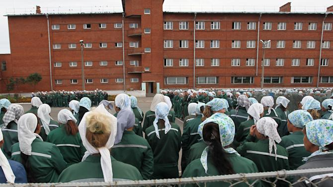 "In this photo taken Aug. 22, 2012 imprisoned women stand during a morning inspection at a women's prison in a town of Sarapul, central Russia. Two members of the punk band Pussy Riot will serve their sentence in a penal colony far from Moscow that is like what a former inmate describes as a ""nasty Girl Scout camp."" Although Russia's prison system is a far cry from Stalin's gulag, the principle remains the same: to isolate people from their families and wear them down through ""corrective labor,"" which for women usually means hunching over a sewing machine. Maria Alyokhina and Nadezhda Tolokonnikova will have to quickly learn the inner laws of prison life, survive the dire food and medical care, and risk reprisal from inmates either offended by their ""punk prayer"" against President Vladimir Putin or ordered to pressure them by higher authorities. (AP Photo/Yuri Tutov)"