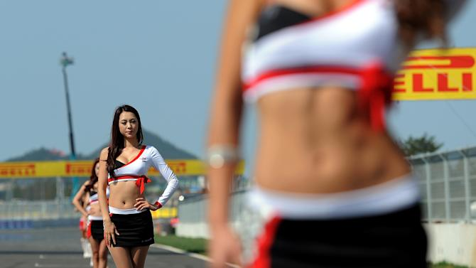 Grid girls pose on the circuit ahead of the start of the Formula One Korean Grand Prix in Yeongam on October 16, 2011.   AFP PHOTO/ MANAN VATSYAYANA (Photo credit should read MANAN VATSYAYANA/AFP/Getty Images)
