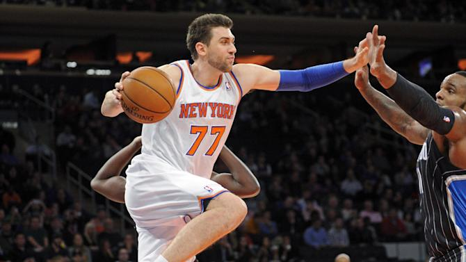 New York Knicks' Andrea Bargnani, left, drives under the basket as Orlando Magic center Glen Davis defends during the second quarter of an NBA basketball game on Friday, Dec. 6, 2013, at Madison Square Garden in New York