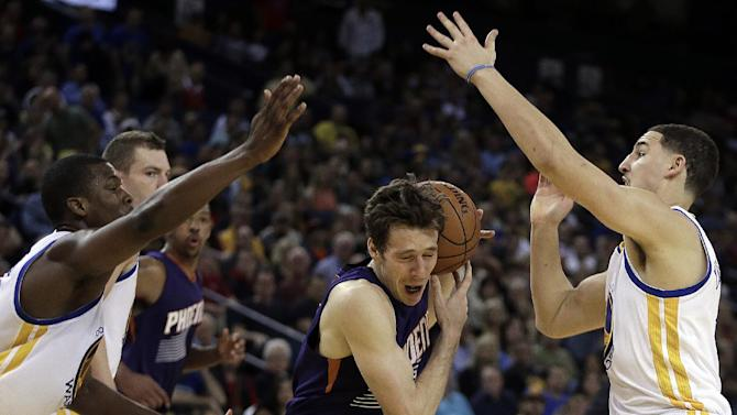 Golden State Warriors' Harrison Barnes, left, and Klay Thompson, right, guard Phoenix Suns' Goran Dragic during the second half of an NBA basketball game Sunday, March 9, 2014, in Oakland, Calif