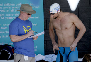 Michael Phelps talks with coach Bob Bowman prior to competing in the men's 100 meter butterfly preliminary, Thursday, April 16, 2015, at the Arena Pro Swim Series in Mesa, Ariz. (AP Photo/Matt York)