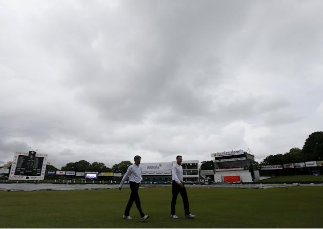 Umpires Llong and Tucker walk off the field after an inspection of the ground condition after the rain, on the first day of third and final test cricket match between India and Sri Lanka in Colombo