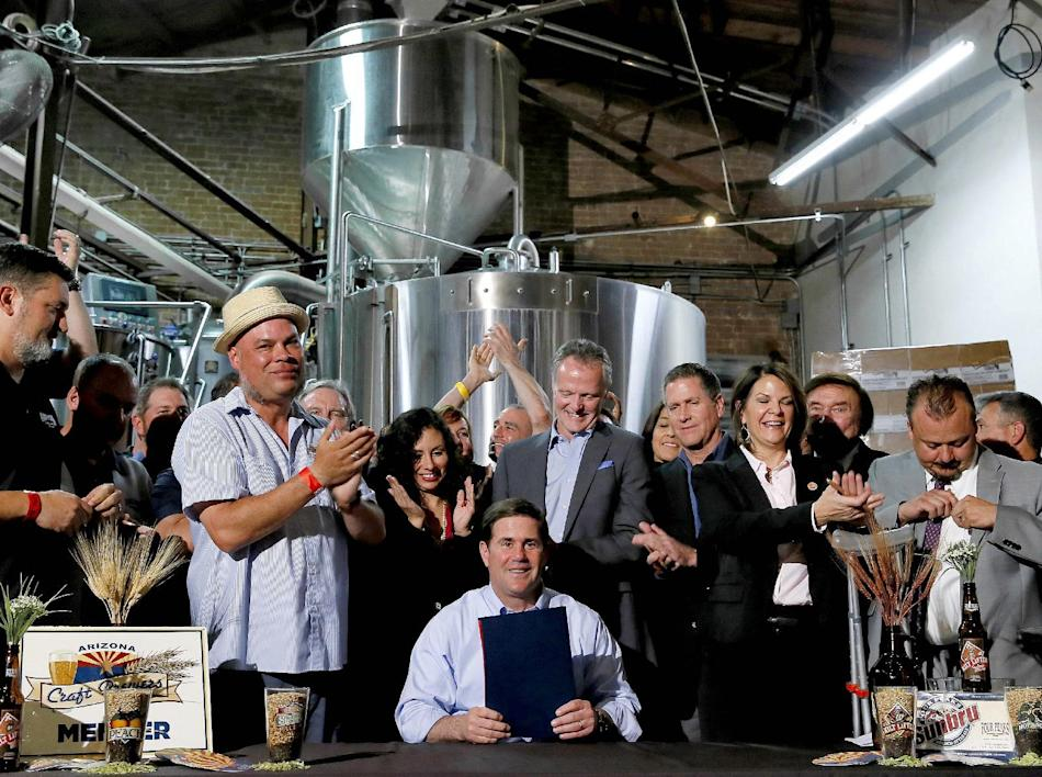 Supporters clap after Arizona Gov. Doug Ducey, center, signed Senate Bill 1030, Tuesday, March 31, 2015, at Four Peaks Brewery in Tempe, Ariz. The bill allows microbreweries to keep running their rest