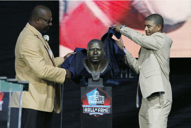 Former NFL player Chris Doleman, left, and his presenter, son Evan Doleman, nveil his bust during his induction into the Pro Football Hall of Fame, Saturday, Aug. 4, 2012, in Canton, Ohio. (AP Photo/T