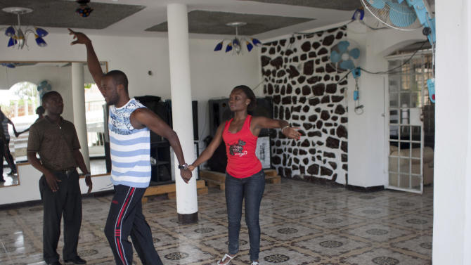 "In this Aug. 3, 2012 photo, professional dancer Georges Exantus, left, teaches a member of a professional dance group as they prepare for a concert in Port-au-Prince, Haiti. Exantus thought he'd never dance again. The earthquake three years ago in Haiti's capital flattened the apartment where he was living, where he spent three days trapped under a heap of jagged rubble. After friends dug him out, doctors amputated his right leg just below the knee. Israeli doctors and physical therapists who came to Haiti after the quake sent him to Israel for surgery and rehabilitation. Three years later, the 32-year-old professional dancer is back on the floor, spinning away as he does the salsa, cha-cha and samba. A prosthetic leg doesn't hold him back. ""As long as I'm living,"" Exantus says, ""I'm going to dance."" (AP Photo/Dieu Nalio Chery)"