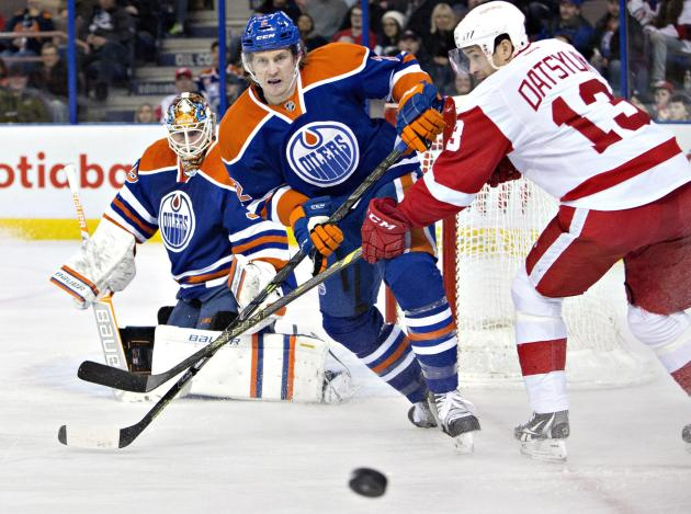 FILE - In this Jan. 6, 2015, file photo, Detroit Red Wings' Pavel Datsyuk (13) and Edmonton Oilers Jeff Petry (2), center, battle for the puck during first period NHL hockey action in Edmonton, Al