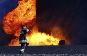 A firefighter stands near the fire of a storage oil …