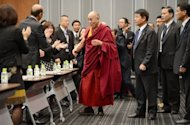 Tibet's spiritual leader Dalai Lama (C) is welcomed by Japanese parliament members at the upper house members' office building in Tokyo on November 13, 2012. The Dalai Lama urged Japanese lawmakers Tuesday to visit Tibet to find out the reasons for a spate of self-immolations