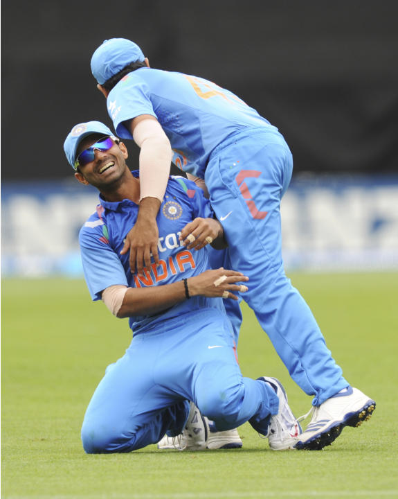 India's Ajinkya Rahane, left, is hugged by Rohit Sharma after taking the catch to dismiss New Zealand's Jessie Ryder for 17 in the fifth and final one-day international cricket match in Wellington