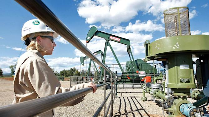 In this Aug. 26, 2009 file photo, Kourtney Hardwick, BP Florida operations manager, looks over a methane gas well site east of Bayfield, Colo. The well pad now has three gas wells that have been drilled and are producing natural gas. A new report from the U.S. Environmental Protection Agency has dramatically lowered estimates of how much of a potent greenhouse gas is being leaked by the natural gas industry. The EPA now estimates that in 2011 the natural gas industry released 10 percent less methane into the atmosphere than it did in 1990. The new figure comes after the EPA estimated last year that those methane admissions had risen about 15 percent since 1990. (AP Photo/Jerry McBride, File)