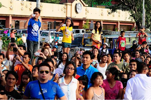Spectators take photos of their favorite actresses and actors during the 2012 Metro Manila Film Festival Parade of Stars on 23 December 2012.(Angela Galia/NPPA Images)