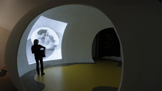 "In this photo taken Monday Nov. 19, 2012, a visitor looks at the photo of Spanish artist Salvador Dali (1904-1989) called 'Memoire Prenatale, 1941' by Philippe Halsman during the presentation to the press of the exhibition ""Dali"" at the Centre Pompidou modern art museum, in Paris. A major retrospective of Salvador Dali in Paris aims to rewrite the art history books, reconciling for the first time the last decades of his life _ when he was accused of money-making self-publicity through numerous television appearances _ with his earlier, respected Surrealist period. (AP Photo/Francois Mori)"