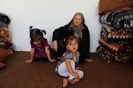A mother and her children, Afghan refugees, are pictured on September 22, 2013 at an UNHCR centre in Herat after being deported from Iran