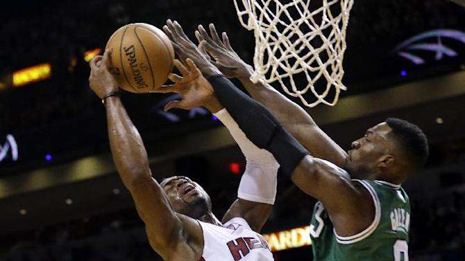 Miami Heat's Dwyane Wade, left, is fouled by Boston Celtics' Jeff Green (8) during the first half of an NBA basketball game Saturday, Nov. 9, 2013, in Miami