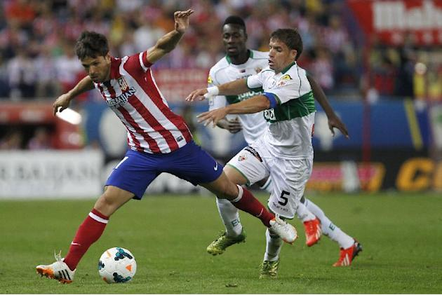 Atletico's Diego Ribas, left, battles for the ball with Elche's Rivera, right, during a Spanish La Liga soccer match between Atletico de Madrid and Elche at the Vicente Calderon stadium in Mad