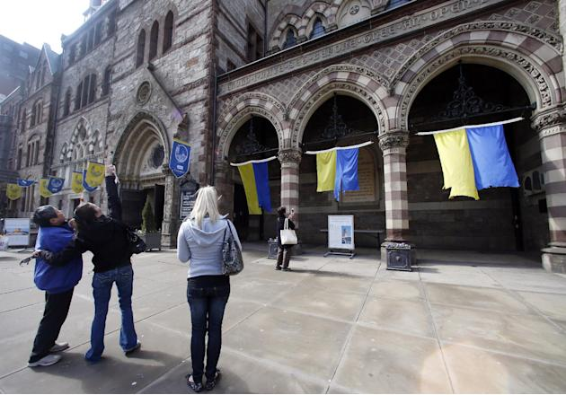 Visitors look at an artist's display of tattered blue and gold banners hanging outside the Old South Church on Boylston Street in Boston, Thursday, April 17, 2014. The banners flew last year throu