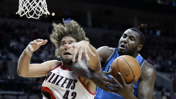 Dallas Mavericks center DeJuan Blair, right, battles for a rebound with Portland Trail Blazers center Robin Lopez during the first half of an NBA basketball game in Portland, Ore., Saturday, Dec. 7, 2013